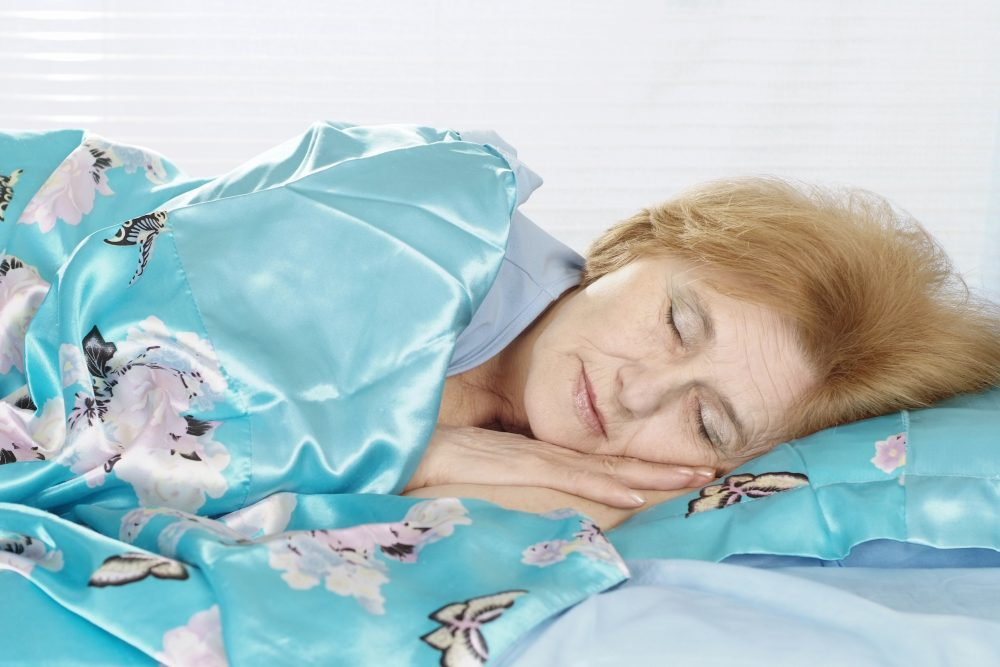 Happy elderly woman in bed
